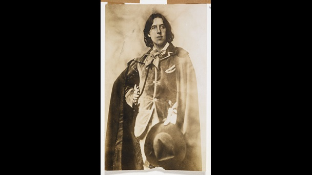 Photograph of Oscar Wilde in a velvet cloak, suit and holding a hat