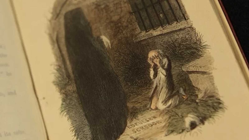 Crop of an illustration from A Christmas Carol depicting Scrooge kneeling in graveyard with face in hands, before the cloaked figure of Christmas Yet to Come