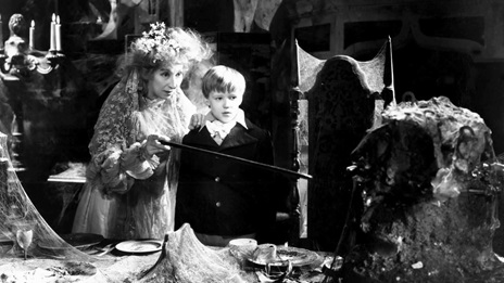 Film still from the 1946 production of Great Expectations, showing Miss Havisham with her arm around Pip as a young boy. The table and furniture are covered in cobwebs