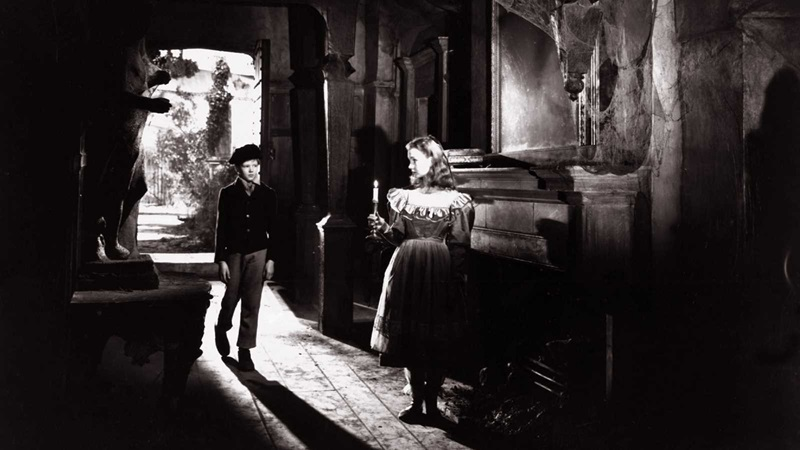 Film still from the 1946 production of Great Expectations, showing Pip and Estella standing inside Satis House