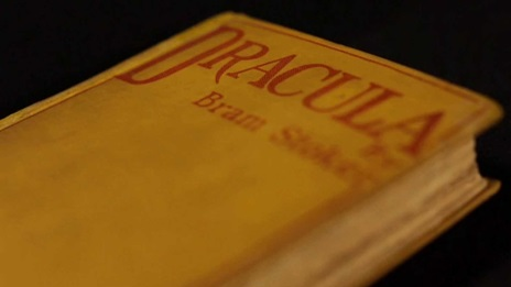 Shot of the first edition of Fracula by Bram Stoker with bright yellow cover and red text