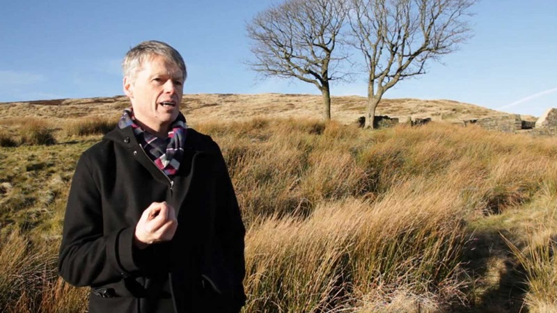Professor John Bowen speaking to camera on the moors around Haworth, a single tree is in the background