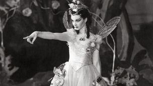 Black and white photograph of Vivien Leigh as  Titania, with fairy wings, pointing and looking to the left