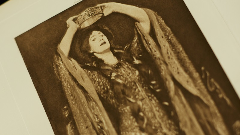 Photograph of actress playing Lady Macbeth, holding crown above her head