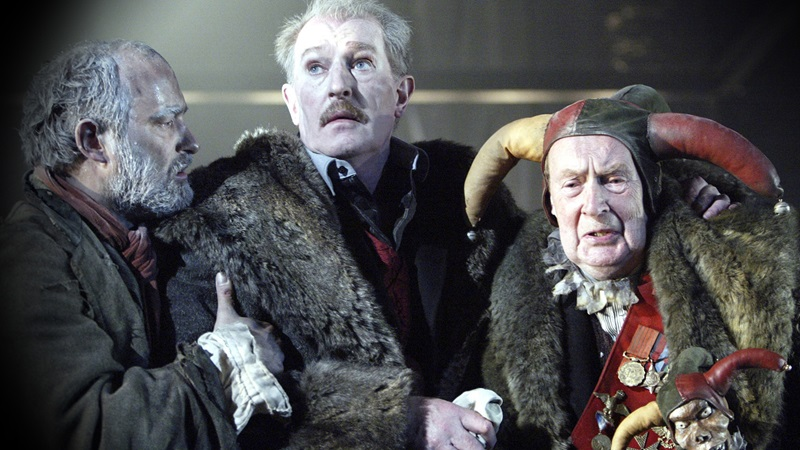 Photograph of a contemporary production of King Lear, showing King Lear holding the hand of the Fool, who wears a jester hat