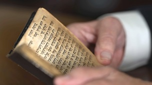 A pair of hands holding a printed Hebrew prayer book.