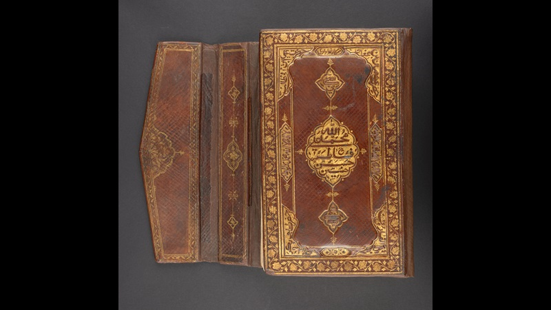 The bindings of Tipu Sultan's personal Qur'an, a burgundy leather background with gold embossed design. There is a border around the outside with a geometric pattern in the centre.