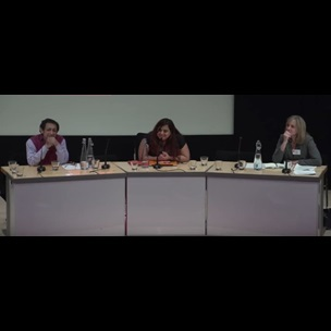 A still image from a video showing Abhijit Gupta and Padmini Ray Murray sat at a desk on stage alongside a member of the British Library receiving a question from an audience member. Part of a panel talk which was part of The Academic Book in the South conference, that took place at The British Library on 7-8 March 2016.