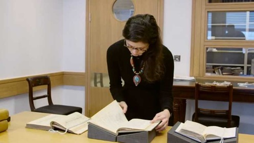 A colour photograph showing Nur Sobers-Khan, Lead Curator at the British Library, in a room turning the page of an open book which is sitting in a foam rest on top of a table. Beside the book are two more open books sat in rests.