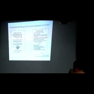 A still image from a video showing a member of Jadavpur University standing behind a lectern on stage. Projected onto the wall behind them to their right is one of the presentation slides from a paper written by Abu Jar Md. Akkas, Deputy Editor of New Age newspaper, Bangladesh. The paper 'Dating the first Bengali block print specimen: A review' was presented as part of The Book Unbound conference, held at Jadavpur University on 14 and 15 July 2017.