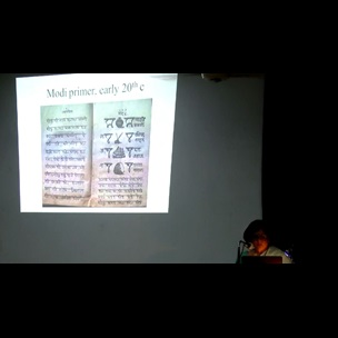 A still image from a video showing Prachi Deshpande, Assistant Professor of History at Centre for Studies in Social Sciences, Kolkata, standing at a lectern. Behind her is a projection of a slide from her presentation 'Scribes, Scripts and Speed: Marathi Handwriting in the Age of Print'. This presentation was given as part of The Book Unbound conference, held at Jadavpur University on 14 and 15 July 2017.