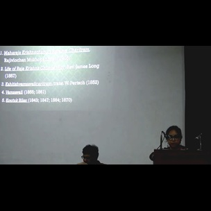 A still image from a video showing Priyanka Basu, Project Curator at the British Library, standing behind a lectern with a projection of her presentation displayed on the wall behind her. Her presentation 'The Many Lives of Raja Krishnachandra Ray: Koutuk Bilas, Biography-Writing and the Introduction of Gopal Bhand in Print in Nineteenth Century Calcutta' was given as part of The Book Unbound conference which took place at Jadavpur University on 14 and 15 July 2017.