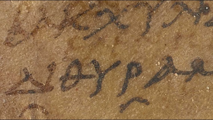 A detail from a 2nd-century papyrus, featuring a parchment sillybos or label with an inscription in Ancient Greek.