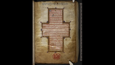 The opening page of a 10th-century Gospel-book, featuring the Letter of Eusebius, written in red ink in a cross-shaped text format and framed in gold.