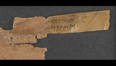 A small fragment of a 2nd-century papyrus scroll, with an attached parchment sillybos, or label, inscribed with the title of a work by Bacchylides.