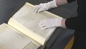 A conservator handling a manuscript with gloves