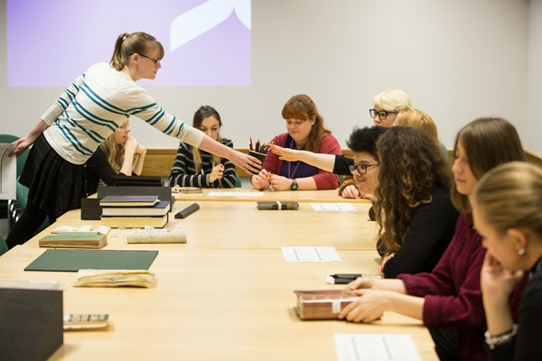 Group of Doctoral students accompanied by a British Library expert studying around a desk