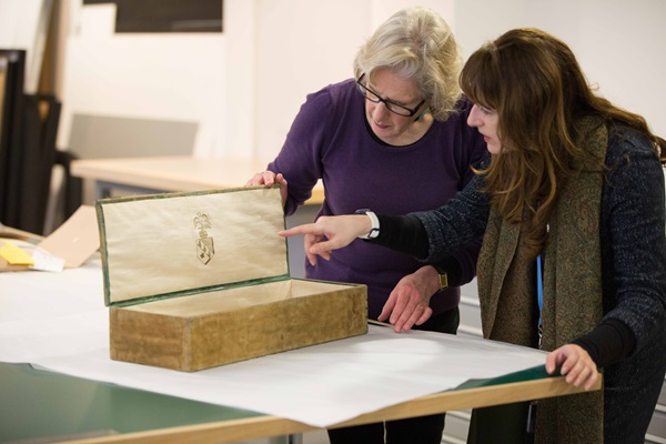 Researcher and conservator examine a collection item together