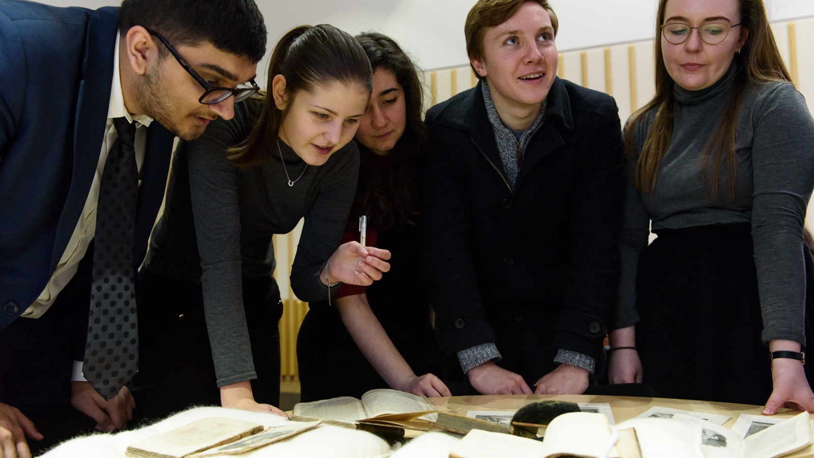 Photograph of group of students studying collection item material on table