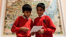Two school students talking in front of map on display