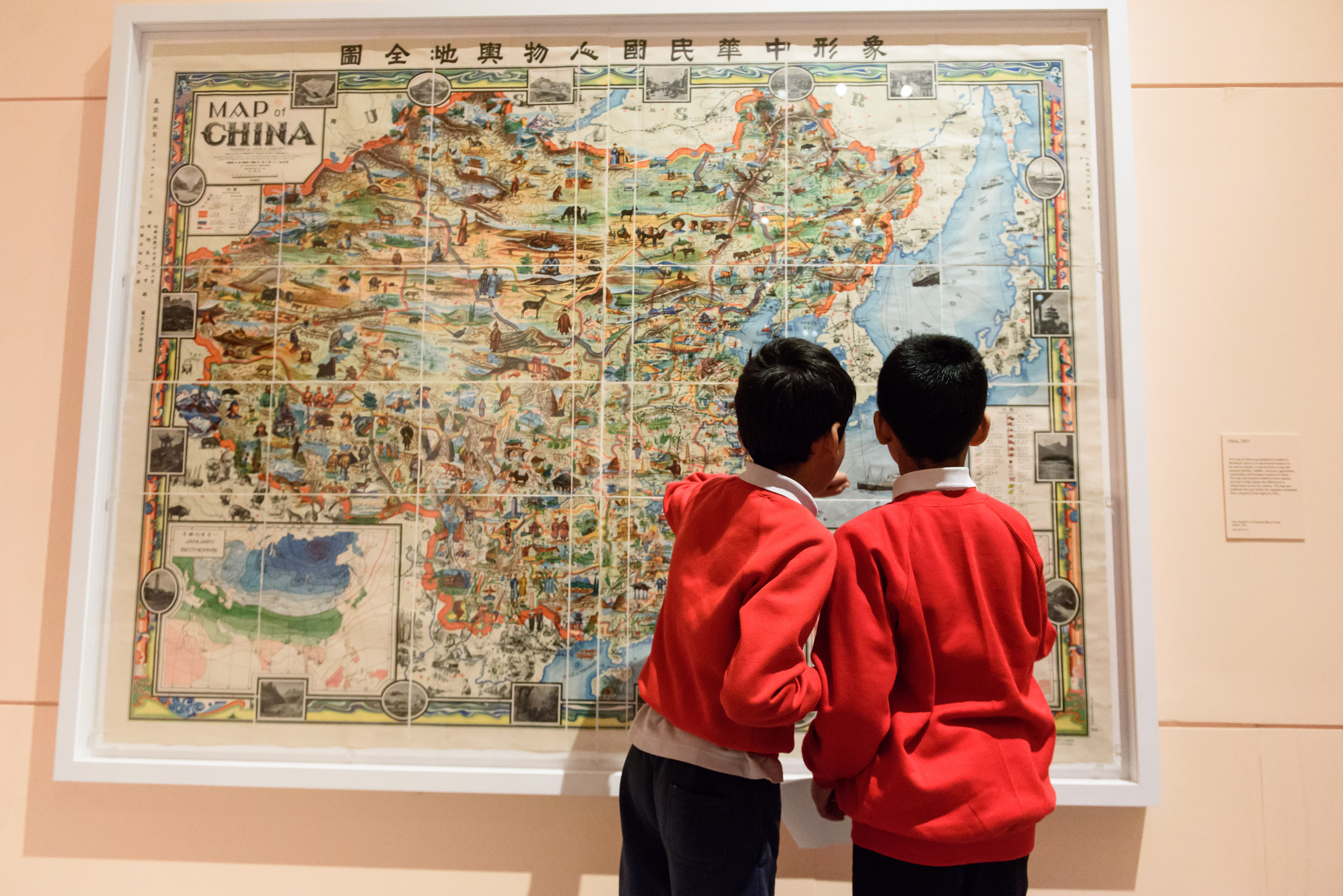 Two school pupils view a map in a gallery
