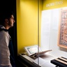 Boy looking at sacred text item in exhibition