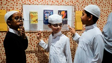 School students looking at children's books on display inside exhibition