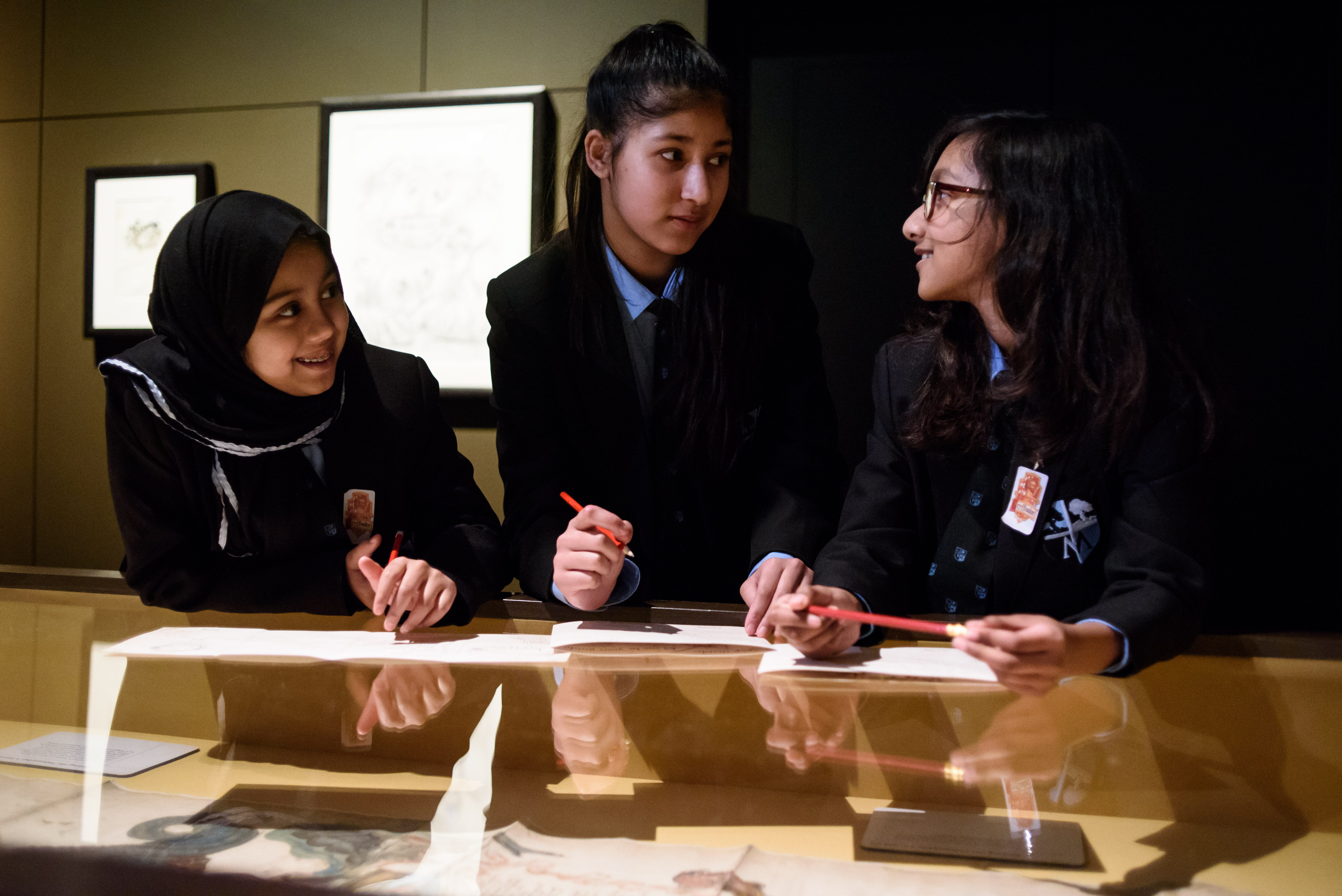 Three school students discuss their task in an exhibition gallery