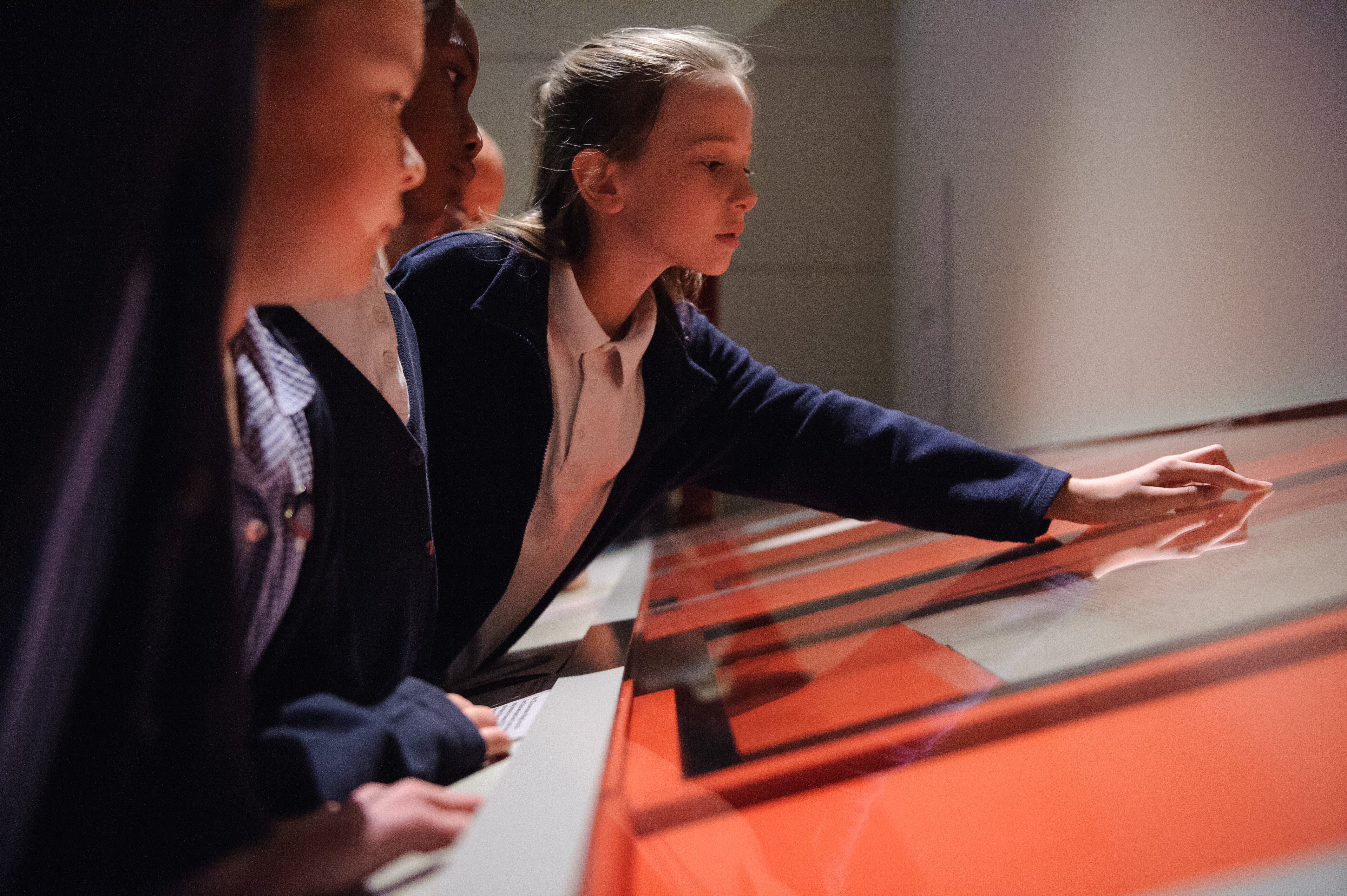 Primary school pupils look through a glass case at a collection item in a schools workshop