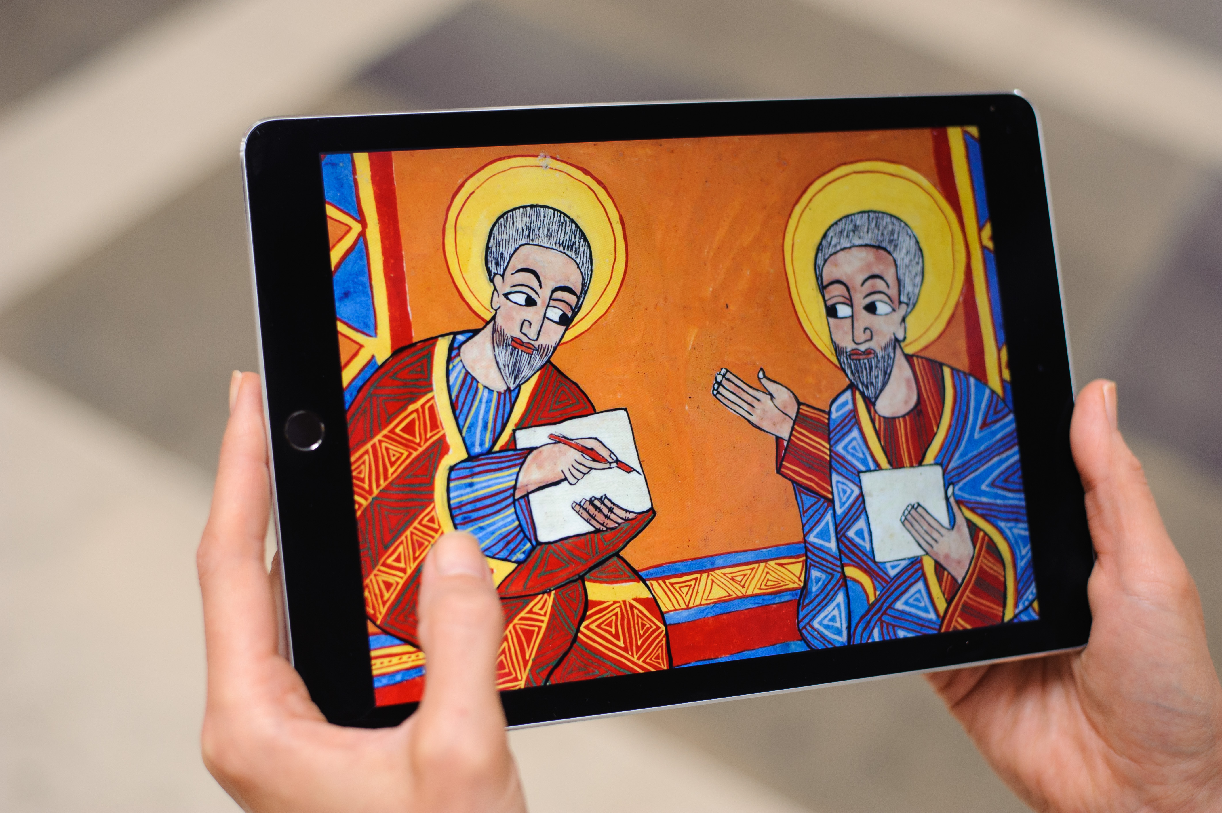 Hands holding an electronic tablet showing a detail from a brightly coloured Ethiopic religious manuscript