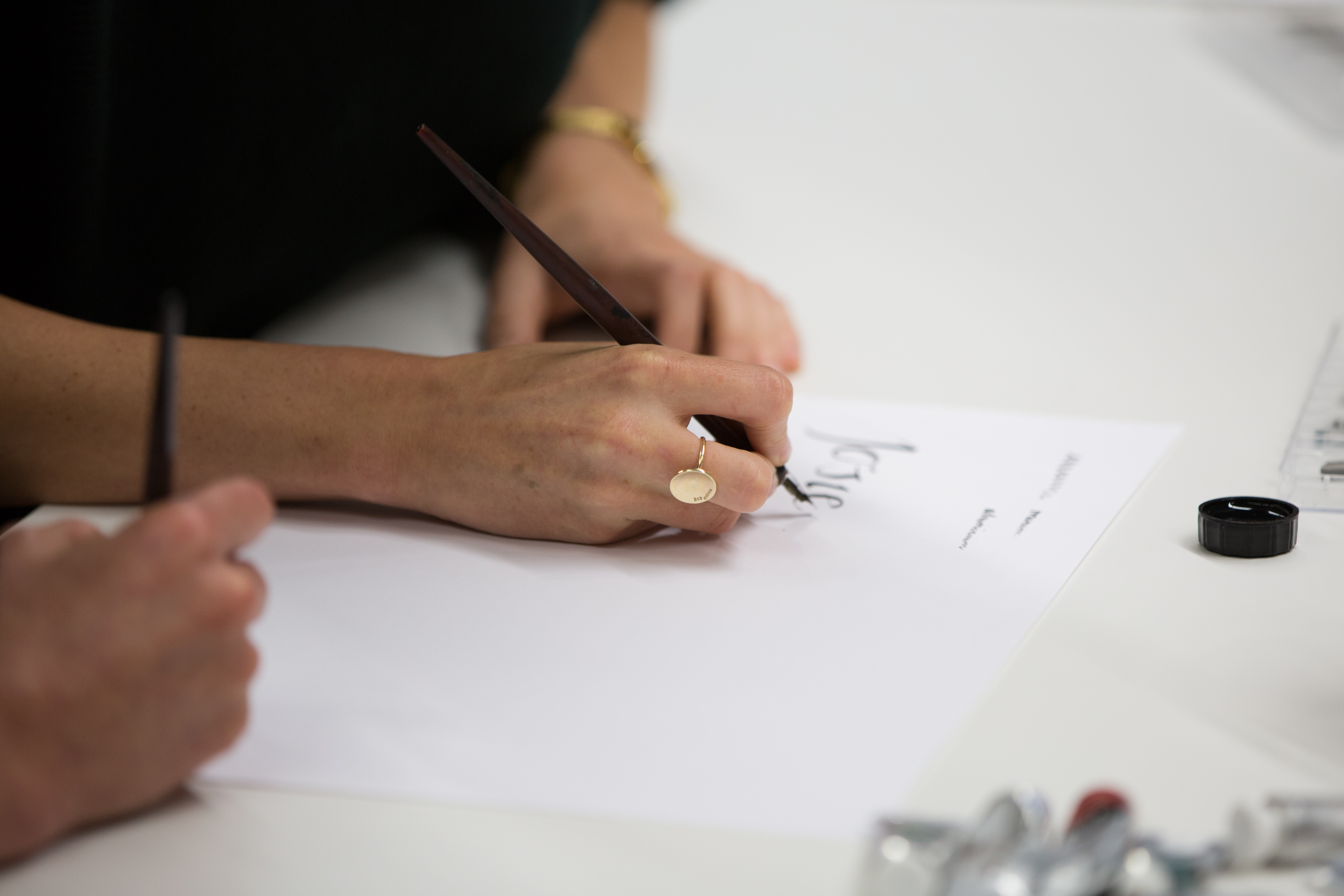 A pair of hands holding a calligraphy pen making black calligraphic letters on a white piece of paper