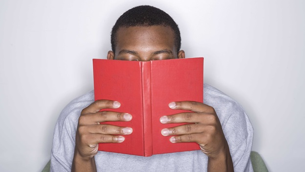 Man holding a book in front of his face.