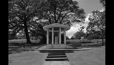 Black and white photograph of a neo-classical rotunda with trees behind it
