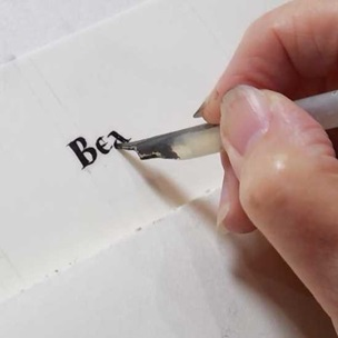 A quill being used to write on vellum.