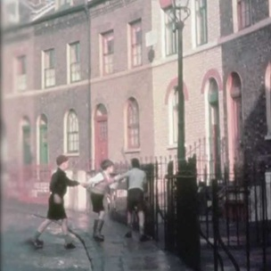 Historical film still of children playing a running game in a street