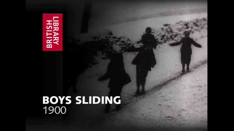 Historical film still of boys sliding down a snowy slope while standing