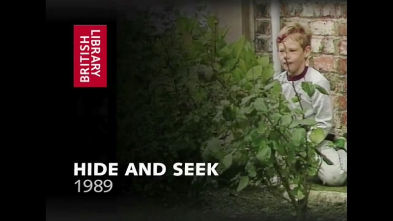 1980s film still of child playing hide and seek, hidden behind a bush