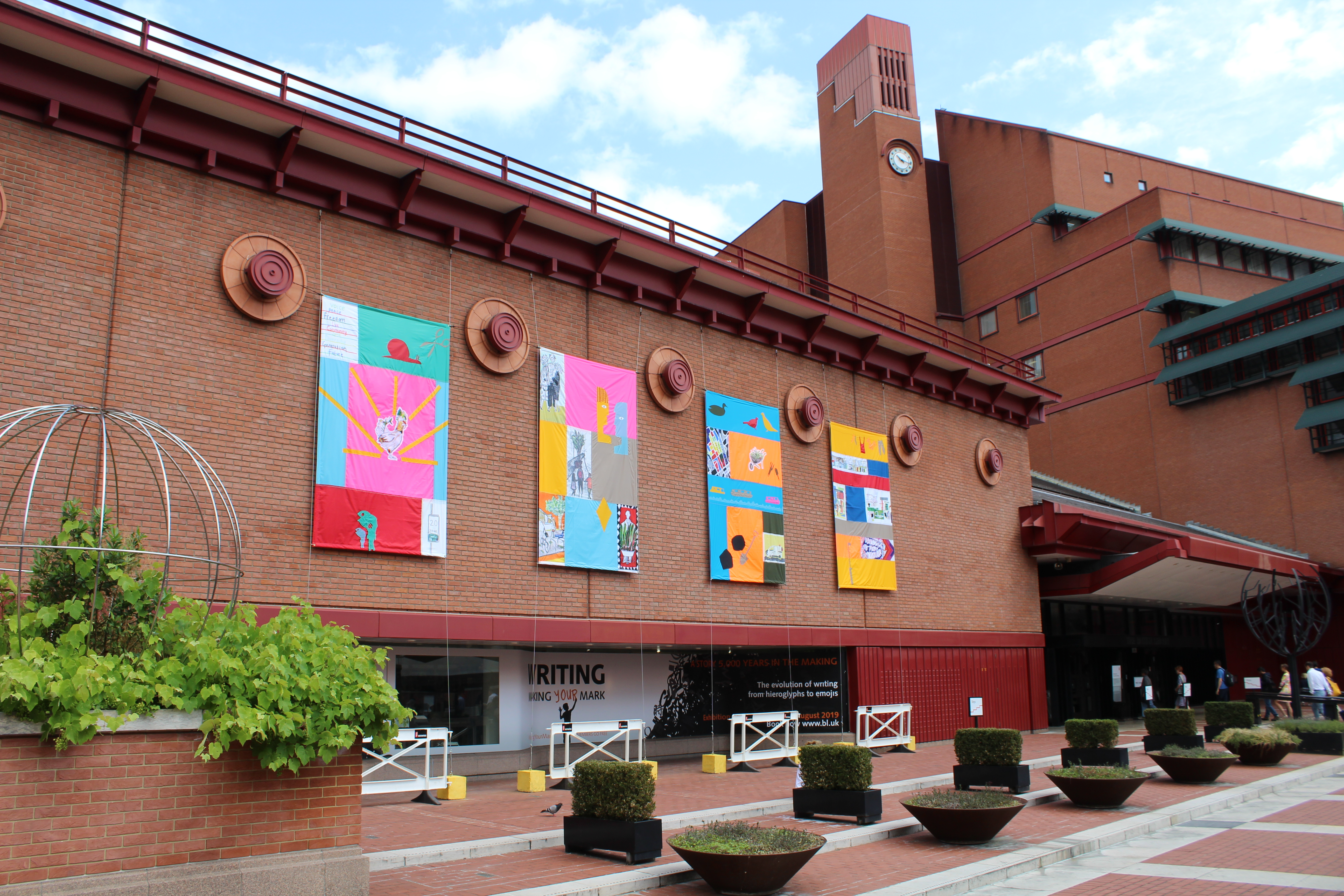 Flags created by Central Saint Martins students with local community groups hang from the British Library for Somers Town Festival