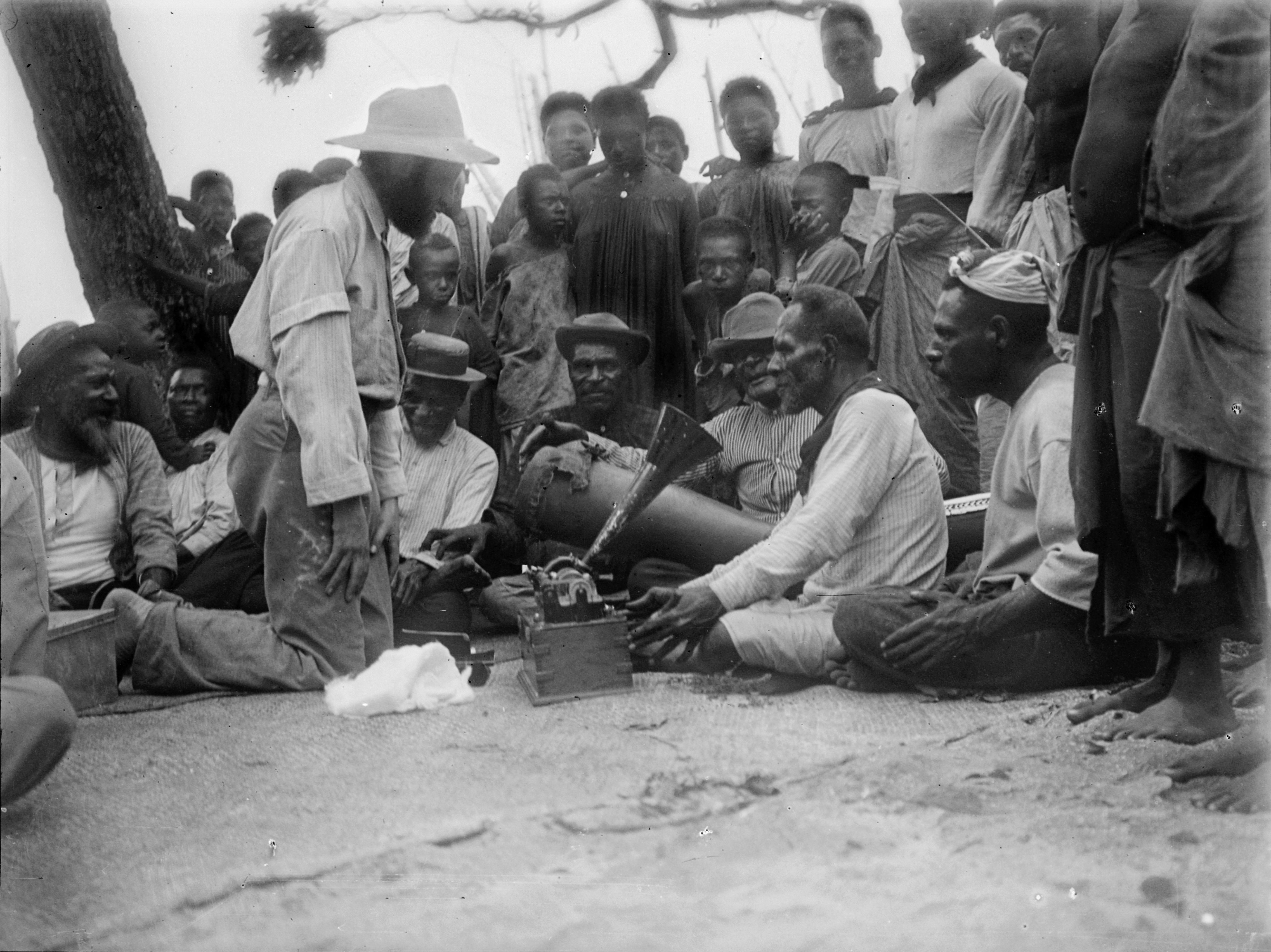Charles Myers recording the sacred songs of the Malo ceremony, with Ulai singing into the phonograph and Gusu playing the drum Wasikor. Mer, Torres Strait, Australia. July 1898. [N.23209.ACH2] Image courtesy of the Cambridge Museum of Archaeology and Anthropology