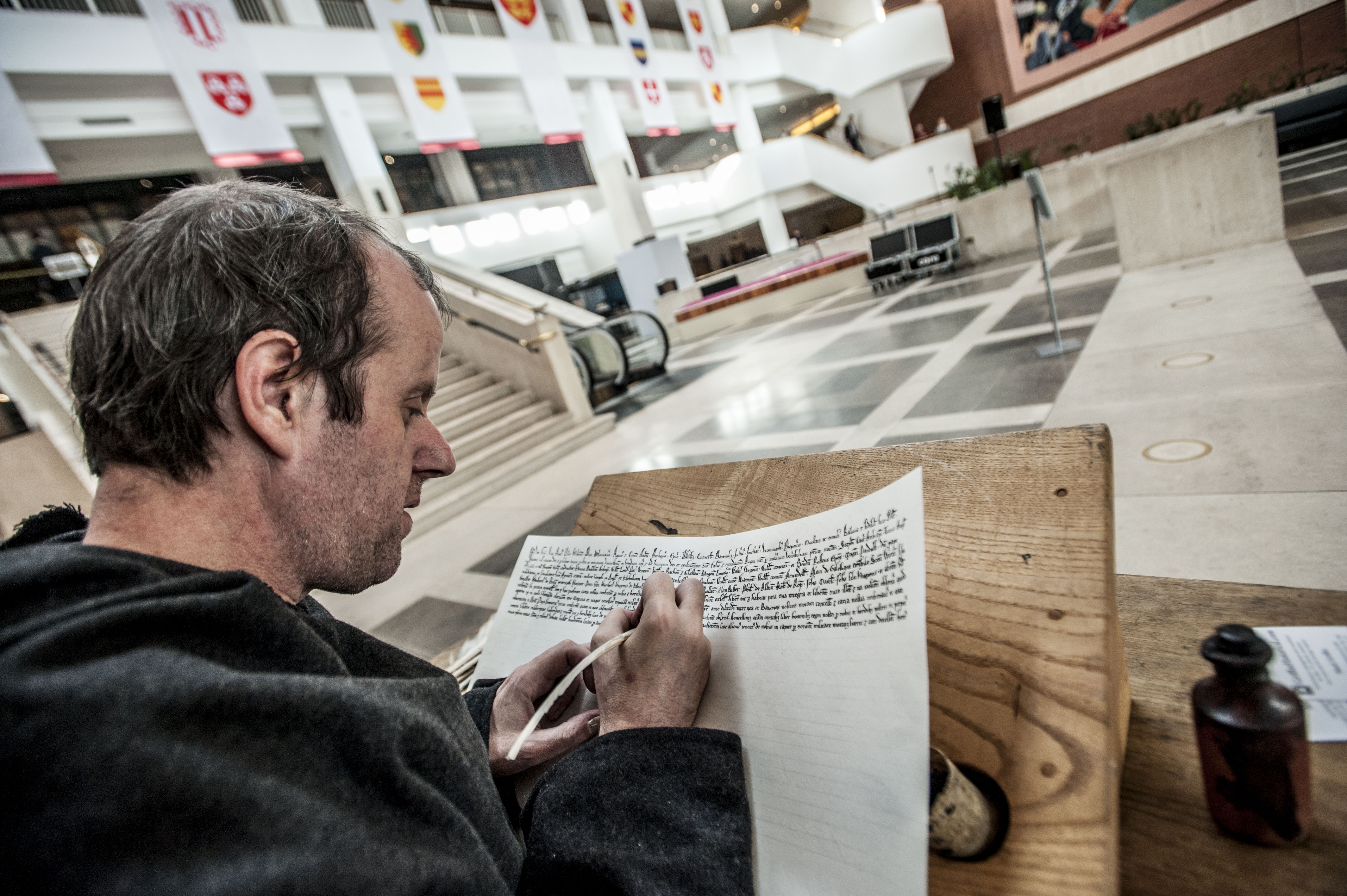 A scribe writes out Magna Carta clauses at the unification day.