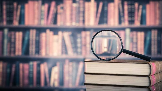 Magnifying glass on top of books in front of book shelves.