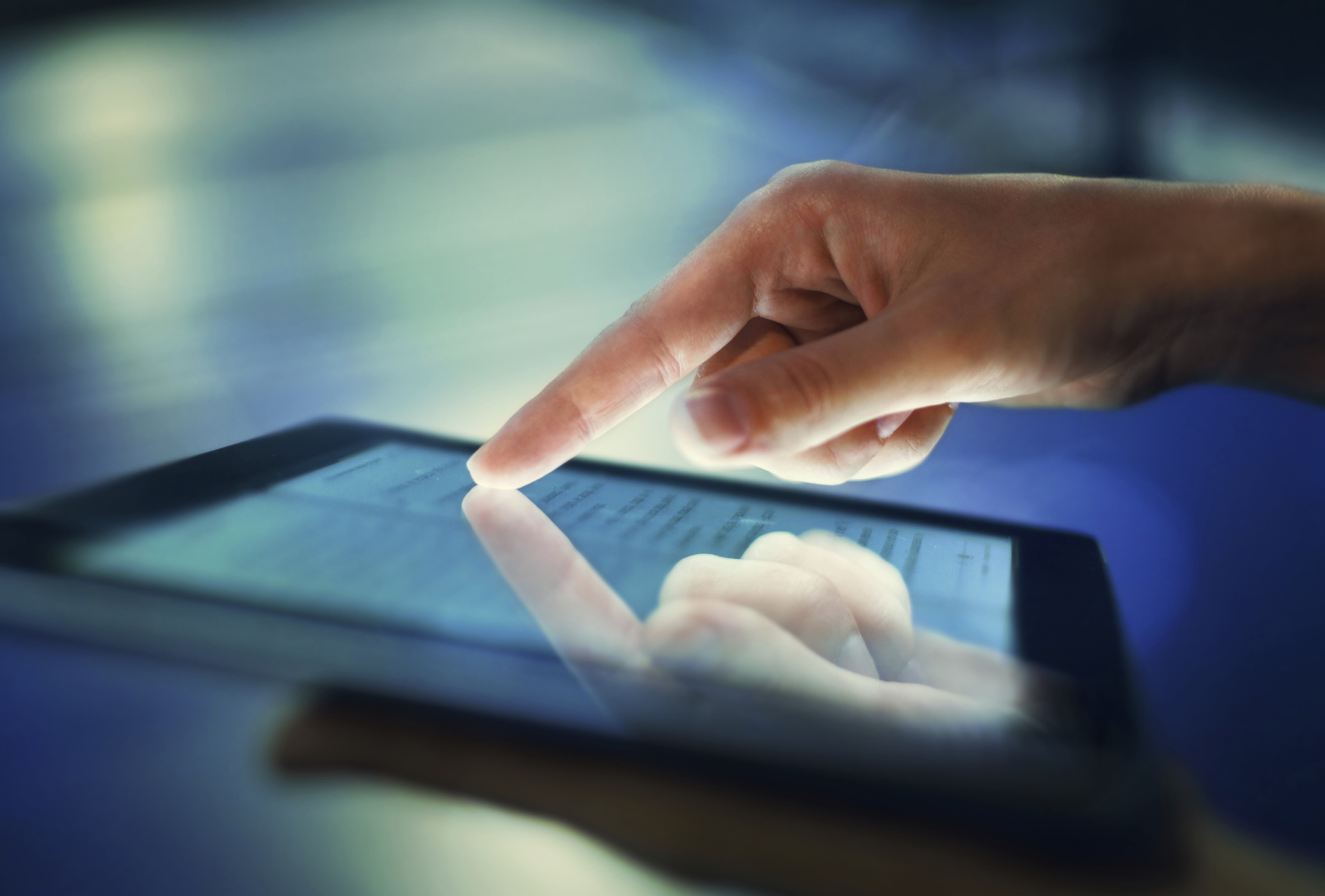 A finger pointing to content on an iPad