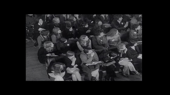 Film still showing seated attendees at a Women's Liberation conference