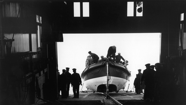 Black and white photograph of a life boat being prepared in a life boat station.