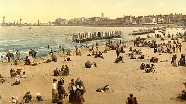 Old Photograph of the beach at Margate. There are crowds of people at leisure in old fashioned dress.