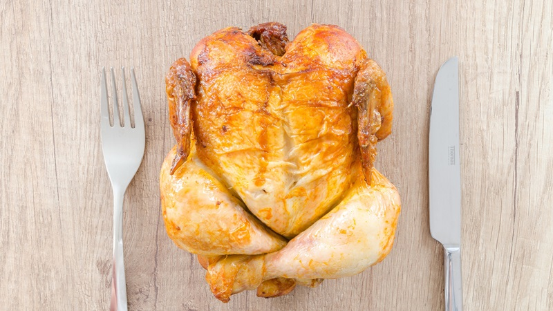 Photograph of a whole roasted chicken in between a knife and fork on a wooden table