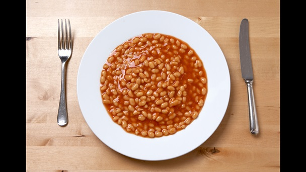 Photograph of a white plate which is full of baked beans. An knife and fork are laid on either side of the plate