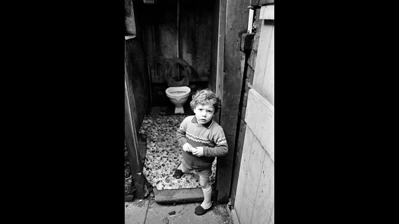 Young child standing in the open doorway of an outside toilet, the toilet is visible behind the child. Black and white photograph