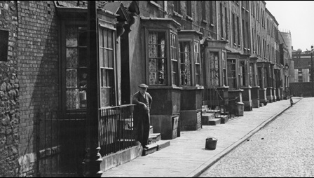 Scene of a Bristolian terrace of houses. A man stands on the step of the house closest to the camera