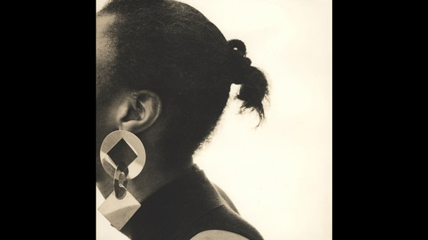 A portrait from Joy Gregory's work Autoportrait. An obscured face turns to the left as a geometrical earring is on show